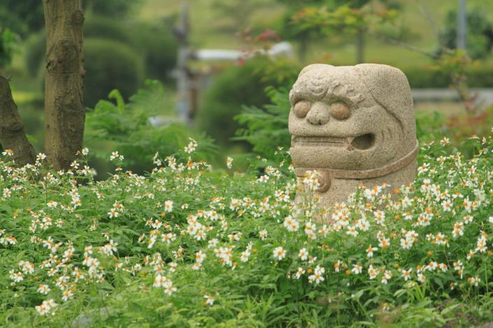 環保公園裡的花叢中,有一尊開心的風獅爺爺,對著祂大笑三聲,煩悶的心,也就開了。