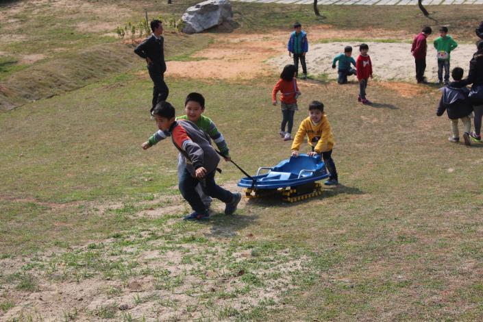三個小男孩拉著滑草車