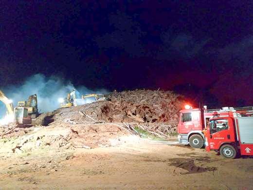圖片內有挖土機、消防車以及冒煙的土堆